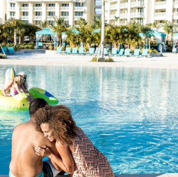 Couple hugging and laughing by the pool at Margaritaville Resort Orlando.